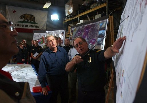President George W. Bush receives a briefing and update on the wildfires from Division Chief John Hawkins of the Califrornia Department of Forestry in El Cajon, Calif., Tuesday, Nov. 4, 2003. White House photo by Eric Draper.