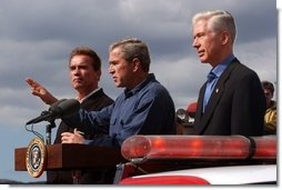President George W. Bush stands with California Governor-elect Arnold Schwarzenegger, left, and California Governor Gray Davis as he addresses firefighters in El Cajon, Calif., Tuesday, Nov. 4, 2003.  White House photo by Eric Draper