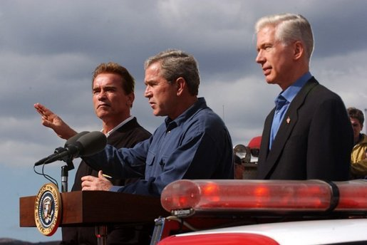 President George W. Bush stands with California Governor-elect Arnold Schwarzenegger, left, and California Governor Gray Davis as he addresses firefighters in El Cajon, Calif., Tuesday, Nov. 4, 2003. White House photo by Eric Draper.