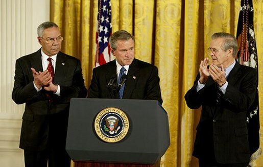 President George W. Bush delivers remarks at the signing of The Emergency Supplemental Appropriations Act for Defense and for The Reconstruction of Iraq and Afghanistan in the East Room Thursday, Nov. 6, 2003. Pictured with the President are Secretary of State Colin Powell, left, and Defense Secretary Donald Rumsfeld. White House photo by Susan Sterner