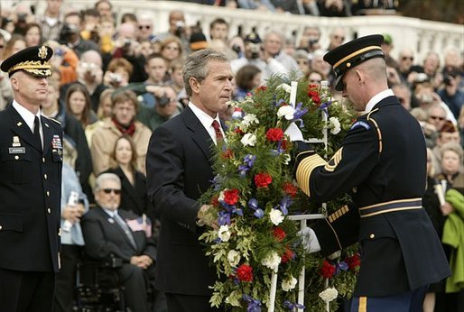 "Honoring those who died in service to America, President George W. Bush lays a wreath at the Tomb of the Unknowns in Arlington Cemetery on Veterans Day Nov. 11, 2003. After the wreath was placed, ""Taps"" was played and a moment of silence was observed. White House photo by Paul Morse."