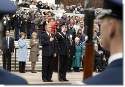 Placing his hand over his heart, President George W. Bush participates in the Wreath Laying Ceremony at the Tomb of the Unknowns in Arlington Cemetery on Veterans Day Nov. 11, 2003. Laura Bush is pictured standing behind the President.  White House photo by Paul Morse