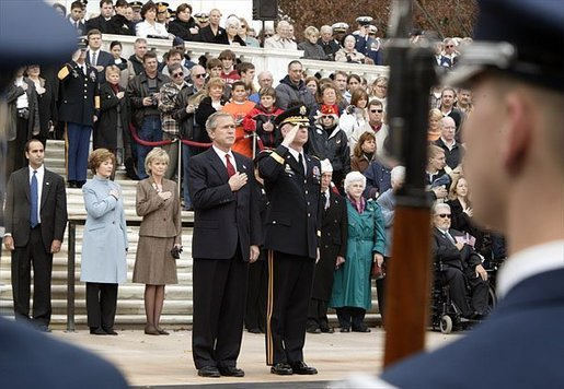 Placing his hand over his heart, President George W. Bush participates in the Wreath Laying Ceremony at the Tomb of the Unknowns in Arlington Cemetery on Veterans Day Nov. 11, 2003. Laura Bush is pictured standing behind the President. White House photo by Paul Morse.