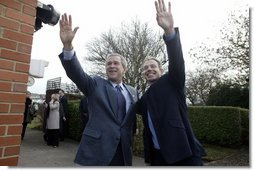 President George W. Bush and Prime Minister Tony Blair wave to onlookers during the President's visit to the Blair's home.  White House photo by Eric Draper