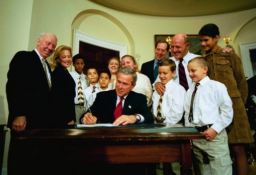 President George W. Bush signs the Adoption Promotion Act of 2003 in the Roosevelt Room December 2, 2003. Pictured with the President are the Chris and Diana Martin family. Their children are Katrina, 13, Ashley, 12, T.J., 11, Kyle, 10, Travis, 10, Dakota, 8, and Terrance, 7. Also pictured are Congressman James Oberstar, far left, Senator Mary Landrieu, and at back right, Congressman Dave Camp. White House photo by Eric Draper.