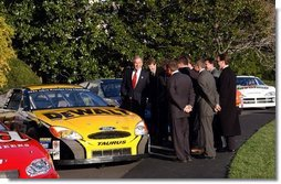 "President George W. Bush jokes with NASCAR racers after looking over the stock cars parked on the South Lawn Tuesday, Dec. 2, 2003. ""I've hosted champions from many sports here at the White House, this is the first time, however, we ever parked stock cars in the South Lawn,"" President Bush said.  White House photo by Tina Hager"