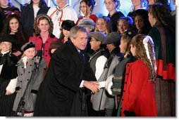 President George W. Bush greets the Voena Children's Choir at the Pageant of Peace after lighting the National Christmas Tree at the Ellipse in Washington DC on Thursday December 4, 2003.  White House photo by Paul Morse