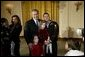 President George W. Bush poses for pictures with a soldier and children during a reception held for children of deployed military personnel at the White House Monday, Dec. 8, 2003. A variety of activities were held for the children, including a performance of selected scenes from The Nutcracker and a visit by Santa Claus. White House photo by Eric Draper