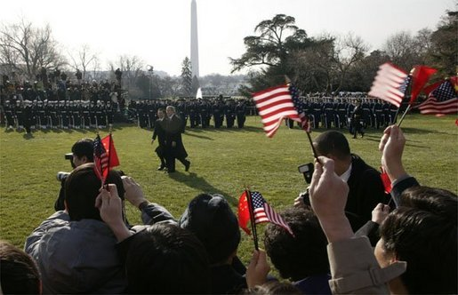 "President George W. Bush and Premier Wen Jiabao of China wave to well-wishers during an Arrival Ceremony on the South Lawn Tuesday, Dec. 9, 2003. ""America and China share many common interests. We are working together in the war on terror. We are fighting to defeat a ruthless enemy of order and civilization. We are partners in diplomacy working to meet the dangers of the 21st century. We are full members of a world trading system that rewards enterprise and lifts nations,"" said President Bush in his remarks. White House photo by Paul Morse"