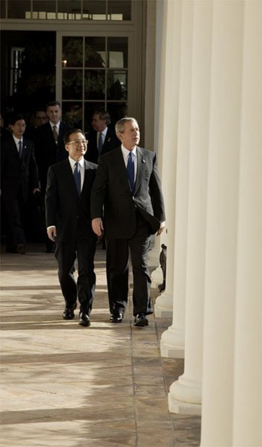 "After the Arrival Ceremony, President George W. Bush and Premier Wen Jiabao of China walk along the Rose Garden Colonnade on their way to the Oval Office Tuesday, Dec. 9, 2003. ""We're going to have extensive discussions today on a lot of issues,"" said the President during an Oval Office meeting with the media. ""We've just had a very friendly and candid discussion. There's no question in my mind that when China and the United States works closely together we can accomplish a lot of very important objectives."" White House photo by Paul Morse"