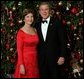 "President George W. Bush and Laura Bush pose for their official Christmas portrait in front of the White House Christmas Tree in the Blue Room, Dec. 7, 2003. This year's holiday theme at the White House celebrates children's storybook characters with, ""A Season of Stories."" More information about the theme and decorations can be viewed at www.whitehouse.gov/holiday/. White House photo by Eric Draper"