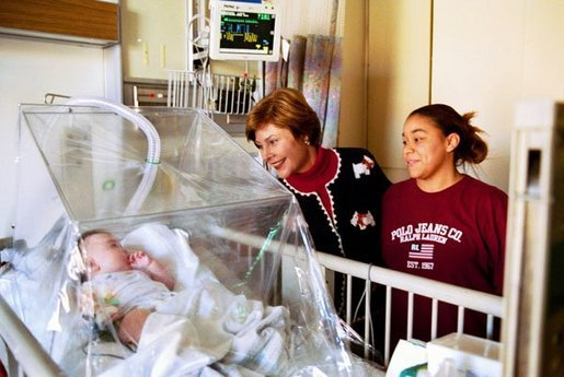 Laura Bush visits with 4-month-old Devon Garner and his mother Tracy Garner at the Children's National Medical Center in Washington, D.C., Friday, Dec. 12, 2003. Mrs. Bush attended the hospital's annual Christmas program. White House photo by Susan Sterner
