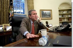 President George W. Bush speaks with British Prime Minister Tony Blair during a phone call in the Oval Office, Sunday morning, Dec. 14, 2003.  White House photo by Eric Draper
