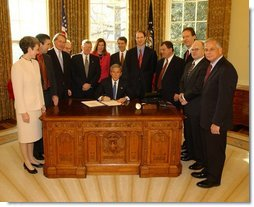 President George W. Bush pauses before signing the Controlling the Non-Solicited Pornography and Marketing Act of 2003, which establishes a framework of administrative, civil and criminal tools to help America's consumers, businesses and families combat SPAM, in the Oval Office Tuesday, Dec. 16, 2003. Pictured with the President are from left to right: Rep. Heather Wilson, (R, NM); Garry Betty, President and CEO of Earthlink; Rep. Edward Markey (D, MA); Rep. Rick Boucher (D, VA); Sen. Conrad Burns (R, MT); Rep. Melissa Hart (R, PA; Sen. Bill Frist (R, TN); Sen. Ron Wyden (D, OR); Rep. Chris Cannon (R, UT); Jonathan Miller, Chairman and CEO of America Online; Maynard Webb, Chief Operating Officer of eBay; Rep. Gene Green (D, TX).  White House photo by Tina Hager