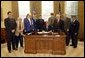 President George W. Bush signs H. R. 2297, the Veterans Benefits Act of 2003, in the Oval Office Tuesday, Dec. 16, 2003. The act expands the benefits program for veterans and their surviving spouses. In attendance are, from left: veterans Dave Thornton of Haymarket, Va.; Charles Stenger of Bethesda, Md.; Carol Near of East Moline, Ill.; Congressman Rob Simmons, R-Conn.; Congressman Chris Smith, R-N.J.; Congressman Lane Evans, D-Ill.; Congressman Henry Brown, R-S.C.; Congressman Bob Filner, D-Calif.; and veteran Guillermo Rumingan of Arlington, Va. White House photo by Paul Morse.