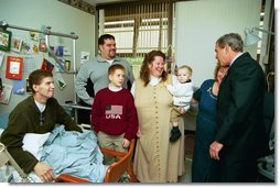 President George W. Bush embraces the mother-in-law of U.S. Army Staff Sergeant Roy Mitchell, who is at left, as other family members look on during the President's visit to Walter Reed Army Medical Center in Washinton, D.C., Thursday, December 18, 2003. President Bush had just presented Sgt. Mitchell The Purple Heart for injuries sustained while serving in Iraq. Sgt. Mitchell is from Milan, Indiana. Others present are, from left, Jerry Stoneking, Zachary Bice and Sgt. Mitchell's wife, Michelle, who is holding their son Jerrett.  White House photo by Eric Draper