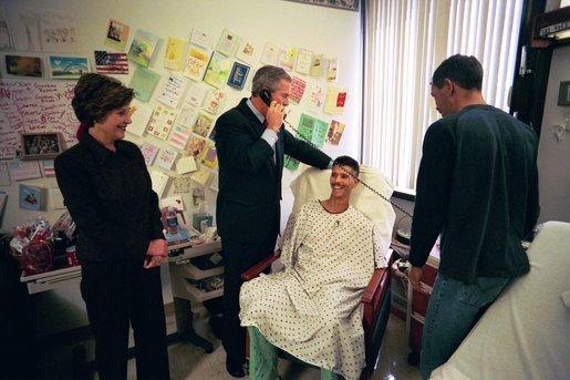 President George W. Bush speaks to a relative of U.S. Army Sergeant First Class Joseph Briscoe, of Liberty, Texas, after presenting Sgt. Briscoe The Purple Heart for injuries he sustained while serving in Iraq. President Bush visited troops at Walter Reed Army Medical Center in Washinton, D.C., Thursday, December 18, 2003. Laura Bush and Sgt. Briscoe's brother, Ira, look on. White House photo by Eric Draper