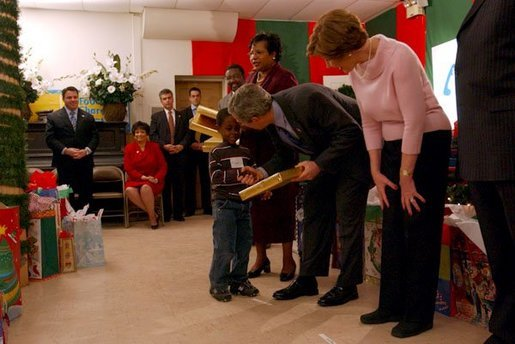 President George W. Bush and Laura Bush take part in the Angel Tree Family Christmas at Shiloh Baptist Church in Alexandria, Va., Monday, Dec. 22, 2003. Began in 1982 by Prison Fellowship, the program helps provides Christmas gifts to children who has an incarcerated parent. White House photo by Tina Hager