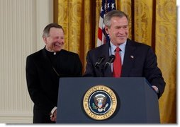 President George W. Bush addresses The National Catholic Educational Association in the East Room Friday, Jan. 9, 2004. The Association represents more than 200,000 educators serving 7.6 million students in Catholic education at all levels. Pictured with the President is His Excellency Gregory Aymond, Bishop of Austin, Texas.  White House photo by Tina Hager