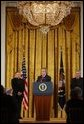 President George W. Bush addresses The National Catholic Educational Association in the East Room Friday, Jan. 9, 2004. Pictured with the President are Bishop Gregory Aymond of Austin, Texas, left and Michael Guerra, President of the NCEA. White House photo by Tina Hager