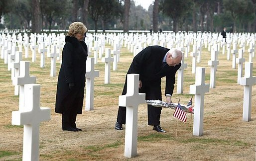 Vice President Dick Cheney places a rose on the grave of Wyoming solider Sgt. John Vannoy while touring the Sicily-Rome American Cemetery with his wife, Lynne, in Nettuno, Italy Jan. 26, 2004. The cemetery inters those who gave their life for the liberation of Italy during World War II. White House photo by David Bohrer.