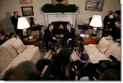 President George W. Bush and President Aleksander Kwasniewski talk with the press in the Oval Office Tuesday, Jan. 27, 2004. After their meeting, President Bush hosted a lunch for President Kwasniewski.   White House photo by Eric Draper