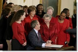 President George W. Bush and Laura Bush laugh with survivors of heart disease as the President signs the American Heart Month proclamation at the White House Monday, Feb. 2, 2004.  White House photo by Paul Morse