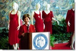 "Laura Bush visits the Red Dress Project Exhibit and delivers remarks to the media after accepting the 2004 Colleges of Cardiology's Honorary Fellowship in New Orleans, Louisiana. "" If we can encourage women to take charge of their health and the health of their families, we can do the same for heart disease. With the many risk factors for heart disease, a woman's greatest risk is ignorance. So I encourage all of you to pull out your favorite red tie or red dress and tell every woman and physician that you know that heart disease doesn't care what you wear."" Monday, March 8, 2004.  White House photo by Tina Hager"