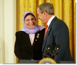 President George W. Bush greets Dr. Raja Habib Khuzai of the Iraqi Governing Council after delivering remarks on Women's Human Rights in the East Room of the White House Fridy, March 12, 2004.  White House photo by Paul Morse