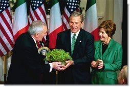President George W. Bush and Laura Bush receive a bowl of Shamrock from Ireland's Prime Minister Bertie Ahren during the annual ceremony celebrating St. Patrick's Day in the Roosevelt Room Wednesday, March 17, 2004.  White House photo by Tina Hager