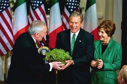 President George W. Bush and Laura Bush receive a bowl of Shamrock from Ireland's Prime Minister Bertie Ahren during the annual ceremony celebrating St. Patrick's Day in the Roosevelt Room Wednesday, March 17, 2004. White House photo by Tina Hager.