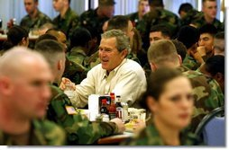 "President George W. Bush and Laura Bush, not pictured, sit down for lunch with soldiers at Fort Campbell, Ky., Thursday, March 18, 2004. ""Here, at one of America's vital military bases, you've built a strong community of people who care about each other, and share the challenges and rewards of army life. America is grateful. America is proud of our military families,"" said the President in his remarks.""   White House photo by Tina Hager"
