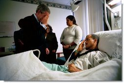 After presenting him The Purple Heart, President George W. Bush salutes U.S. Army Staff Sergeant Santiago Frias of Bronx, N.Y., at Walter Reed Army Medical Center in Washington, D.C., Friday, March 19, 2004. Sgt. Frias was injured while serving in Operation Iraqi Freedom. Also pictured is Sgt. Frias' mother, Cristina DeJesus, left, and his wife, Nejil.  White House photo by Eric Draper