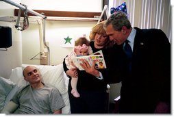 President George W. Bush reads a baby book with U.S. Army Reservist First Lieutenant Brandan Mueller of Webster Groves, Mo., his wife Amanda, and their daughter Abigail at Walter Reed Army Medical Center in Washington, D.C., Friday, March 19, 2004. Lt. Mueller was injured while serving in Operation Iraqi Freedom.  White House photo by Eric Draper