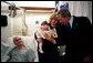 President George W. Bush reads a baby book with U.S. Army Reservist First Lieutenant Brandan Mueller of Webster Groves, Mo., his wife Amanda, and their daughter Abigail at Walter Reed Army Medical Center in Washington, D.C., Friday, March 19, 2004. Lt. Mueller was injured while serving in Operation Iraqi Freedom. White House photo by Eric Draper.