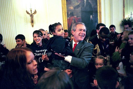 President George W. Bush hugs Kiera Williams, 4, of Spokane, Wash., during a photo shoot with the Children's Miracle Network Champions Across America Representatives in the East Room of the White House Monday, March 22, 2004. The Champions are children who have battled a wide range of challenges, including birth defects, cancer and life-threatening illnesses. They now serve as ambassadors for the network. White House photo by Tina Hager.