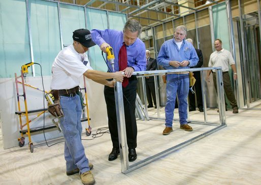President George W. Bush uses a drill to connect a metal wall frame during a tour of the Carpenters Training Center in Phoenix, Ariz., Friday, March 26, 2004. White House photo by Eric Draper
