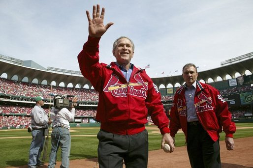 After throwing out the first pitch during the St. Louis Cardinals' season opener against the Milwaukee Brewers, President George W. Bush waves to the crowd as he walks off the field holding his pitched baseball Monday, April 5, 2004. White House photo by Eric Draper