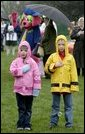 A couple of soaked Easter Egg Roll enthusiasts say the Pledge of Allegiance during the opening ceremonies of the 2004 White House Easter Egg Roll on the South Lawn Monday, April 12, 2004. Despite rain and cold weather, families came out for a morning of Easter eggs and storybook readings. White House photo by Paul Morse.