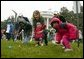 Slipping and sliding, eggs are tossed in rainy race on the South Lawn during the 2004 White House Easter Egg Roll Monday, April 12, 2004. Because of inclement weather, the annual event closed at noon.