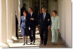 President George W. Bush and Prime Minister Tony Blair walk along the colonnade with their wives Mrs. Laura Bush and Mrs. Cherie Blair after a press conference in the Rose Garden of the White House on April 16, 2004.  White House photo by Paul Morse