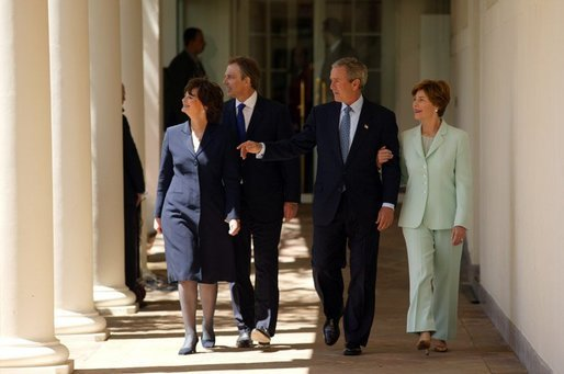 President George W. Bush and Prime Minister Tony Blair walk along the colonnade with their wives Mrs. Laura Bush and Mrs. Cherie Blair after a press conference in the Rose Garden of the White House on April 16, 2004. White House photo by Paul Morse.