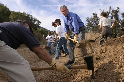 Working alongside volunteers, President Bush works to fill ruts along the Old Boney Trail at the Santa Monica Mountains National Recreation Area in Thousand Oaks, Calif., Aug. 15, 2003. White House photo by Eric Draper.