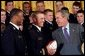 President George W. Bush laughs with Midshipmen Eddie Carthan, left, and team captain Craig Candeto during the presentation of the Commander-In-Chief Trophy to the U.S. Naval Academy football team in the East Room Monday, April 19, 2004. The trophy is awarded to the Service Academy with the year's best overall record in NCAA football games versus the other academies. White House photo by Tina Hager.