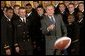 After being presented with a team-signed football, President George W. Bush throws it to an aide during the presentation of the Commander-In-Chief Trophy to the U.S. Naval Academy football team in the East Room Monday, April 19, 2004. The trophy is awarded to the Service Academy with the year's best overall record in NCAA football games versus the other academies. White House photo by Tina Hager.