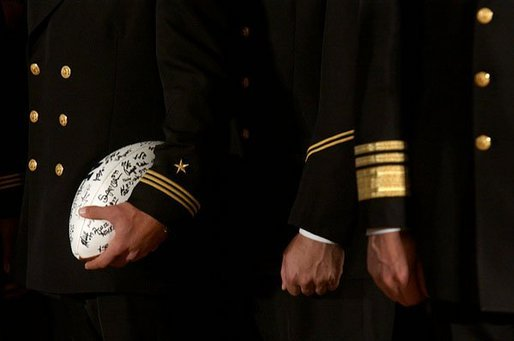 Signed by the entire team as a gift for the President, a football is tucked under the arm of a member of the U.S. Naval Academy football team during the presentation of the Commander-In-Chief Trophy in the East Room Monday, April 19, 2004. White House photo by Tina Hager.