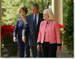 President George W. Bush and First Lady Mrs. Laura Bush walk down the colonnade with Kathleen Mellor of South Kingstown, Rhode Island before presenting her with the 2004 Teacher of the Year award in the Rose Garden of the White House on April 21, 2004.  White House photo by Paul Morse