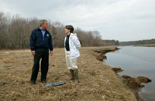 "President George W. Bush on speaks with Research Director Dr. Michele Dionne during a tour of the Wells National Estuarine Research Reserve in Wells, Maine, Thursday, April 22, 2004. ""Up to half of all North American bird species nest or feed in wetlands. About half of all threatened and endangered species use wetlands. There's some endangered species using the wetlands right here on this piece of property,"" said the President in his remarks. White House photo by Eric Draper."