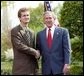 President George W. Bush congratulates Andrew Rominger, 17, of Albuquerque, N.M., on receiving the President's Environmental Youth Award in the East Garden April 22, 2004. White House photo by Susan Sterner.