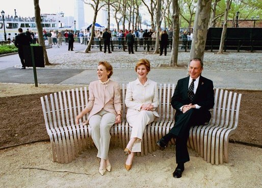 Laura Bush sits on a new park bench with New York City Mayor Michael Bloomberg and The Battery Conservancy Founder and President Warrie Price, left, after the dedication of the 'Gardens of Remembrance' in New York's Battery Park, Monday, May 10, 2004. White House photo by Tina Hager